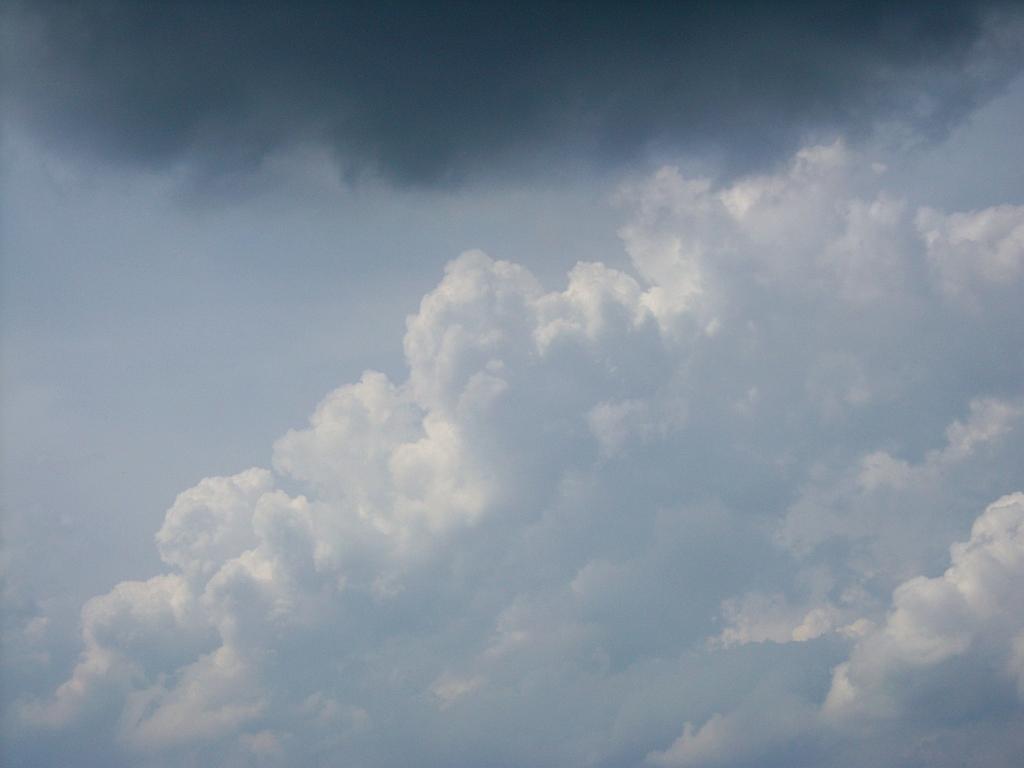 Dunkle regenwolke über blauem himmel mit weißen wolken